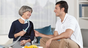 Homecare, Ventilation patient sitting on a couch in her living room with ventilation device, smiling, together with her d a male nurse informing and touching patient's arm